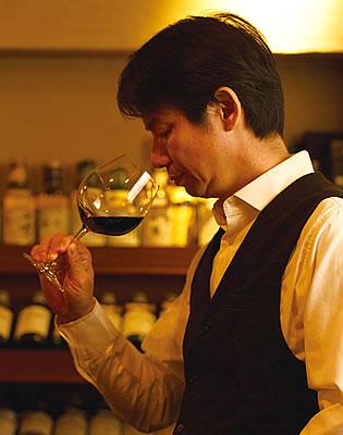 写真:グラスに入った赤ワインの香りを嗅いでいる、杉本浩一さんの横顔。