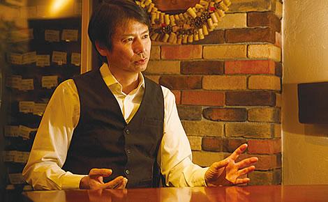 写真:座ってインタビューに答えている杉本浩一さん。