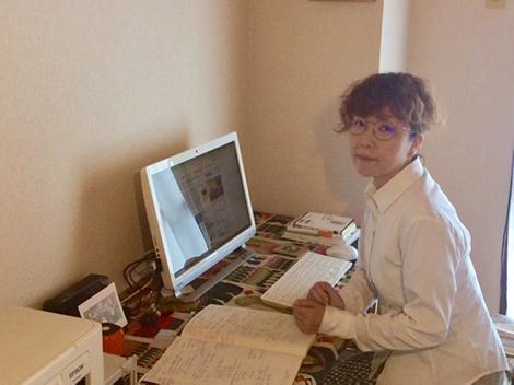 写真:仕事机についている重村さん。机にはPCが置いてある。