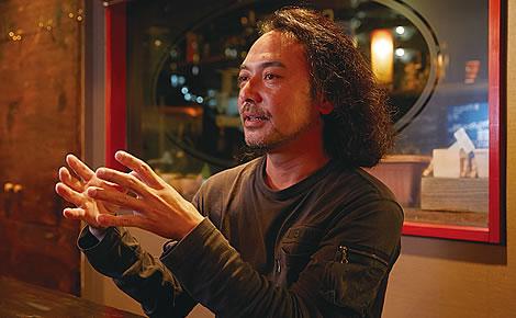 写真:座ってインタビューに答えている川崎満さん。