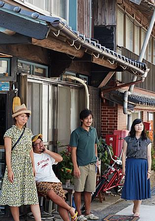 写真:ゲストハウスの外にいる大川さん夫妻と、男性1名・女性1名のお客さん。