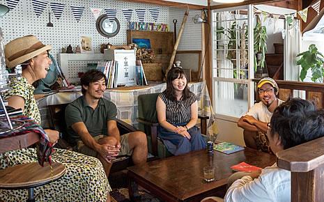 写真:ゲストハウス内でお客さんと談笑している大川さん夫妻。