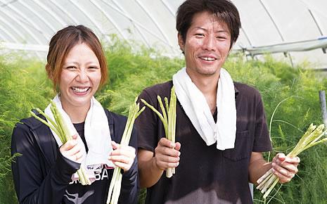 写真:アスパラガスを両手に握って笑顔の平田さん夫妻。