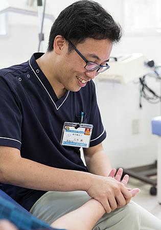 写真:ベッドに寝ている男性の患者さんとその奥に座っている石本さん。