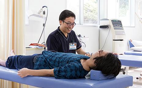 写真:患者さんの右手を膝に乗せて施述している石本さん。