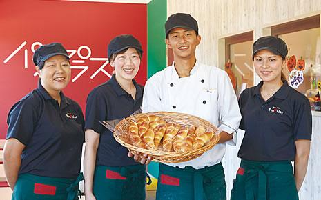 写真:中央には、平たい大きなカゴに入ったパンを持っている大久保さん夫妻。両脇には従業員の女性が1名ずつ並んで立っている。